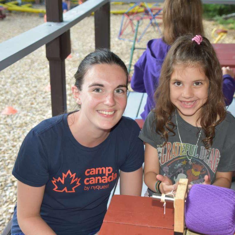 international staff member and camper making bracelet at Canadian Adventure Camp
