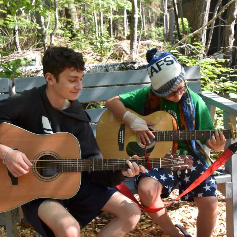 Two campers playing guitar together at camp.