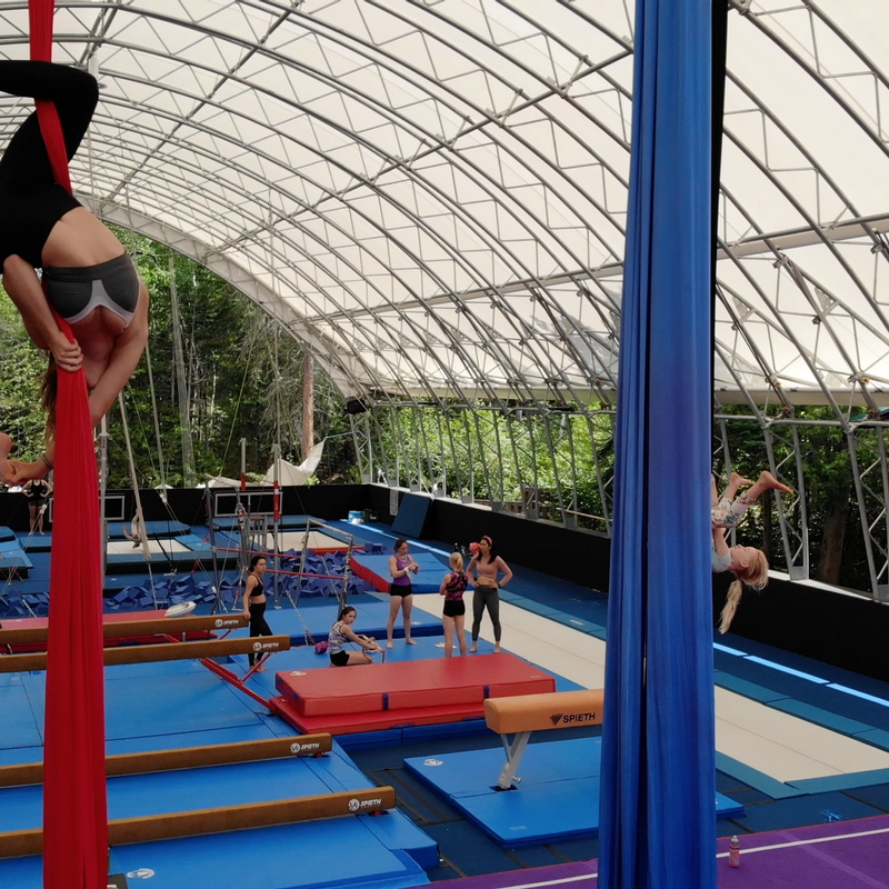 Camper on the silks upside down in the gym at Canadian Adventure Camp