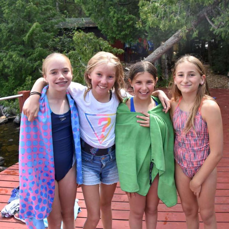 four campers on the dock smiling at the camera at Canadian Adventure Camp