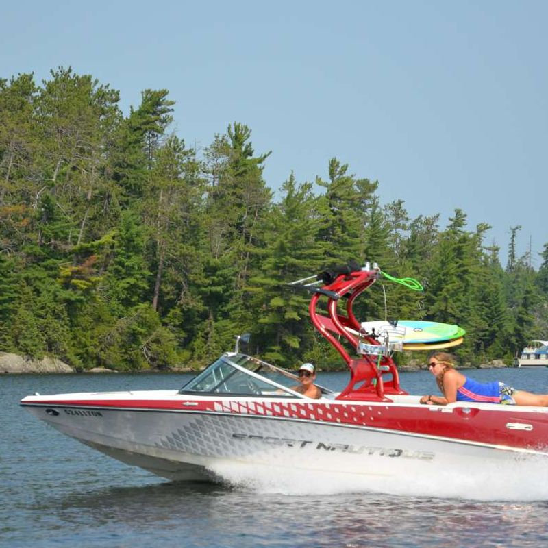 staff driving a boat on the lake at Canadian Adventure Camp