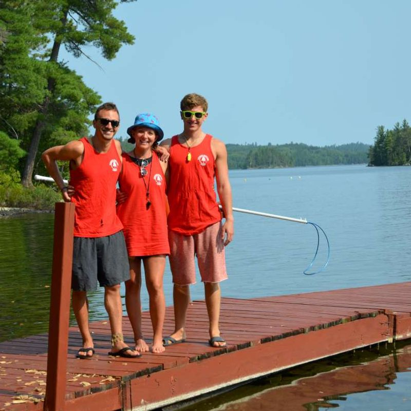 Three lifeguards on the swimming dock at Canadian Adventure Camp