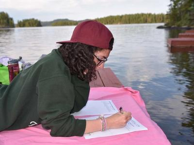 camper writing a letter on the dock at Canadian Adventure Camp