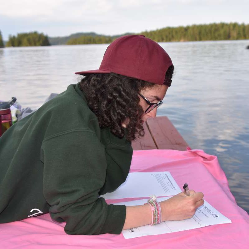 Senior camper writing a bunk note home at Canadian Adventure Camp