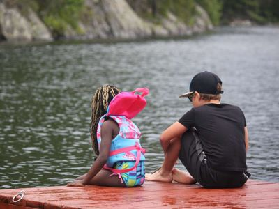 two younger campers sitting together on the dock
