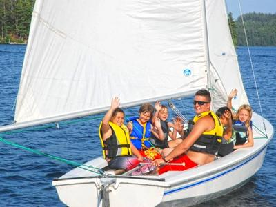 campers and counselor sailing on a boat