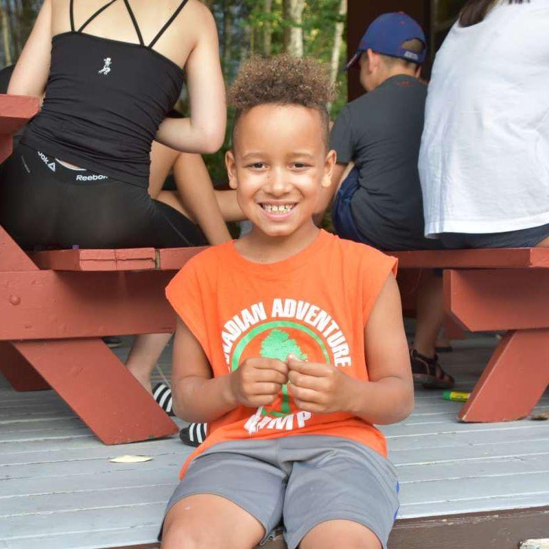 Young camper smiling at the camera at arts and crafts at Canadian Adventure Camp