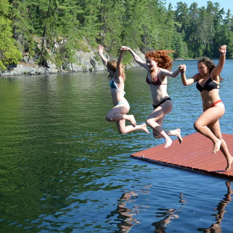 Three campers jumping off the dock into the lake at Canadian Adventure Camp