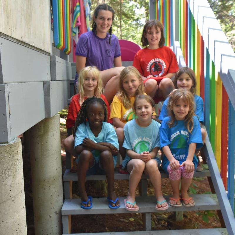 counsellor with group of campers smiling at the camera