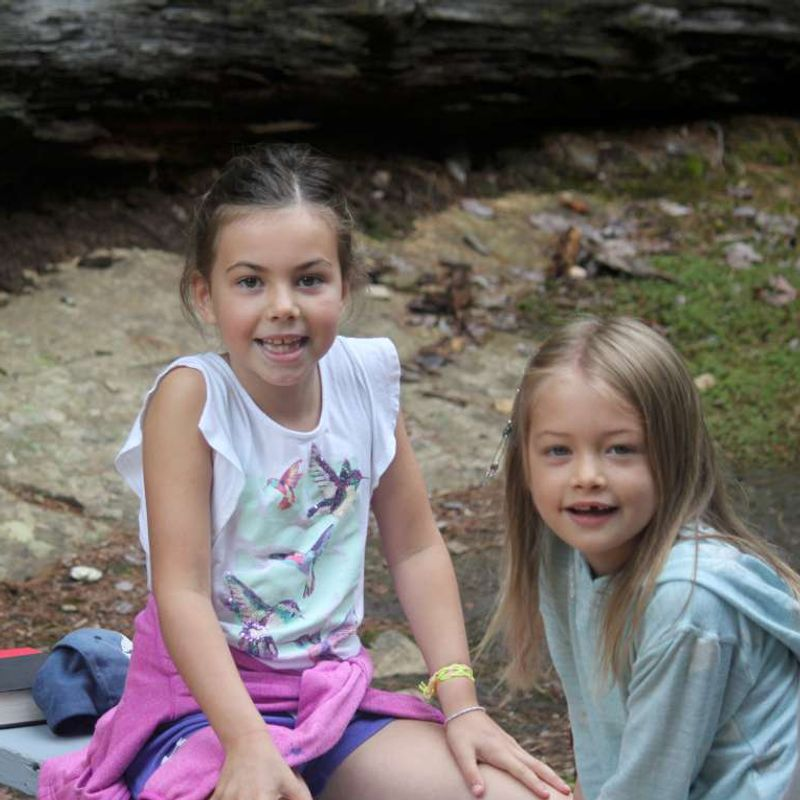 Two young campers sitting and smiling.