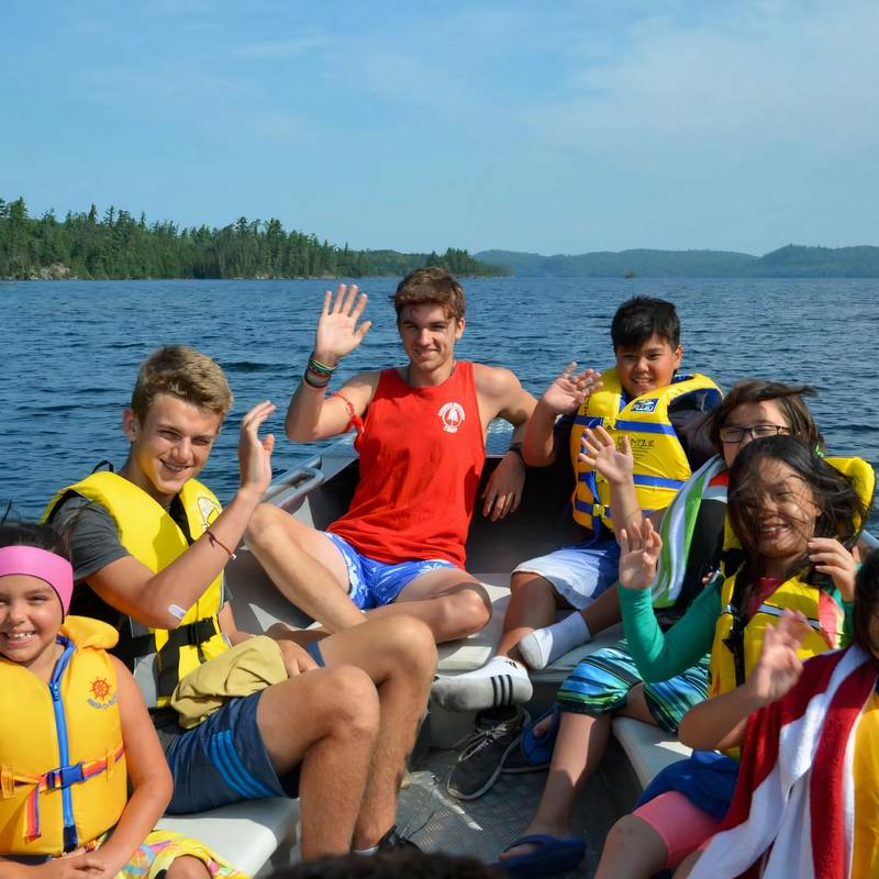 group of campers and lifeguard smiling and waving on a boat