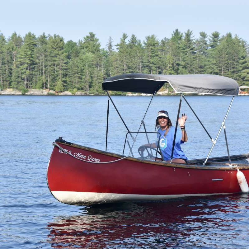 staff driving a camp boat on the lake at Canadian Adventure Camp
