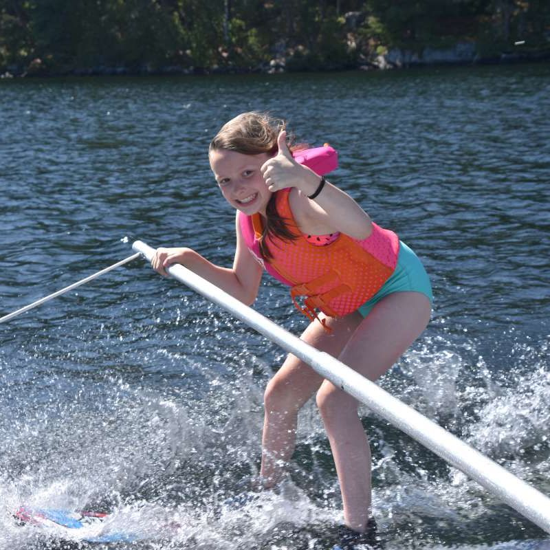young camper with thumbs up waterskiing at Canadian Adventure Camp