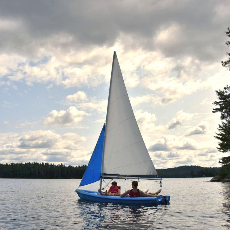 Two campers on a sail boat on the lake at Canadian Adventure Camp