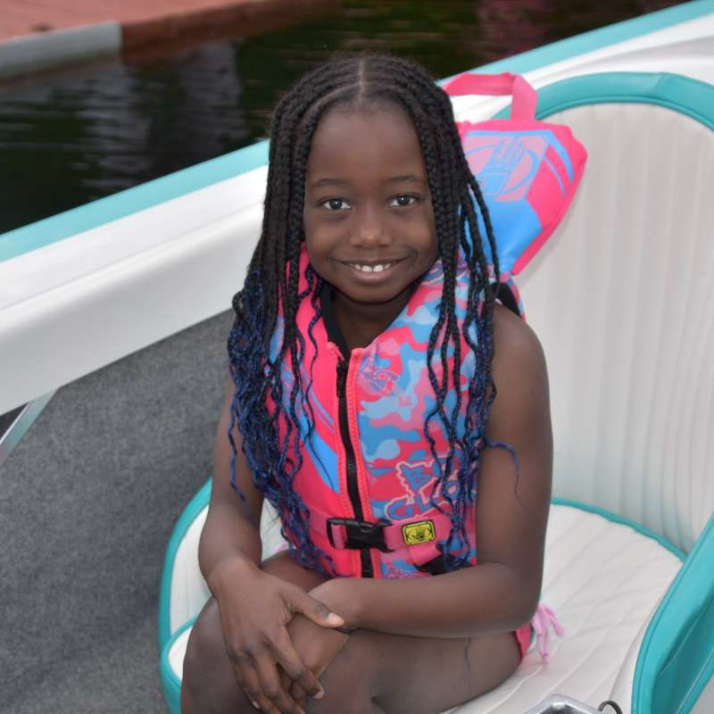 young camper sitting in a boat smiling at the camera at Canadian Adventure Camp