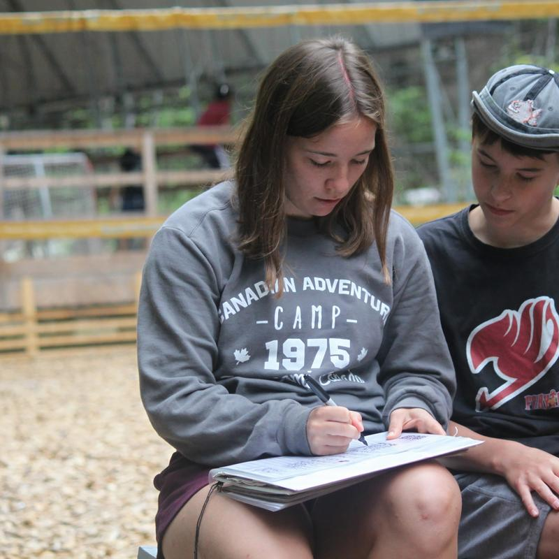 staff writing down notes at Canadian Adventure Camp