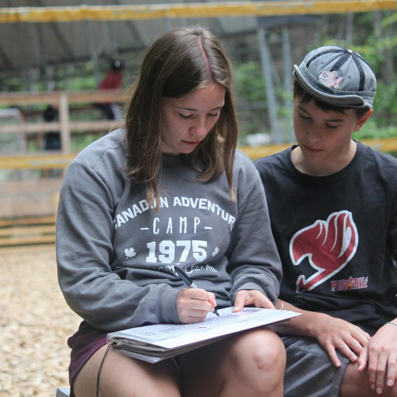 staff writing awards sheet at an activity with camper