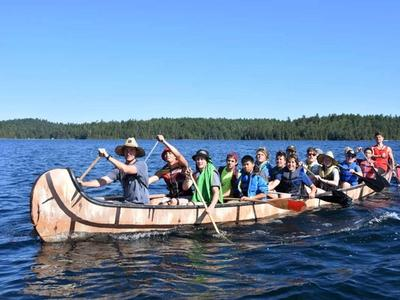 senior camper in the war canoe on the lake at Canadian Adventure Camp
