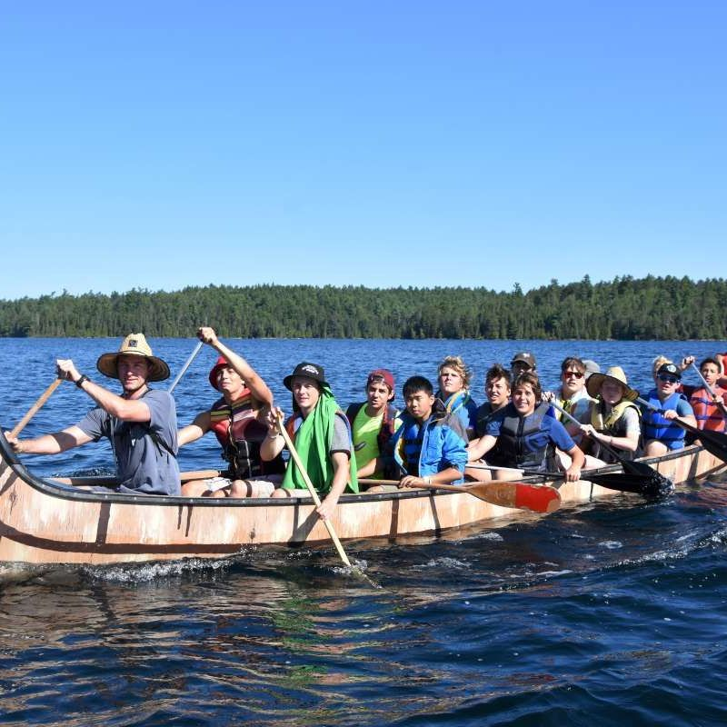 Senior boy campers and counsellors in the war canoe on the lake at Canadian Adventure Camp