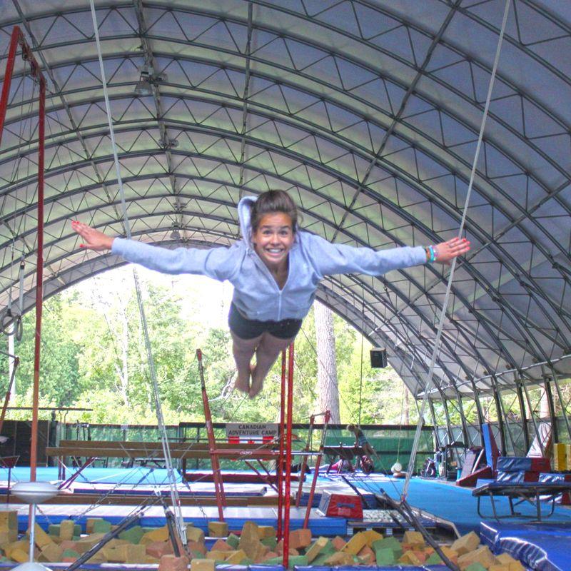 Camper mid-jump on a trampoline.
