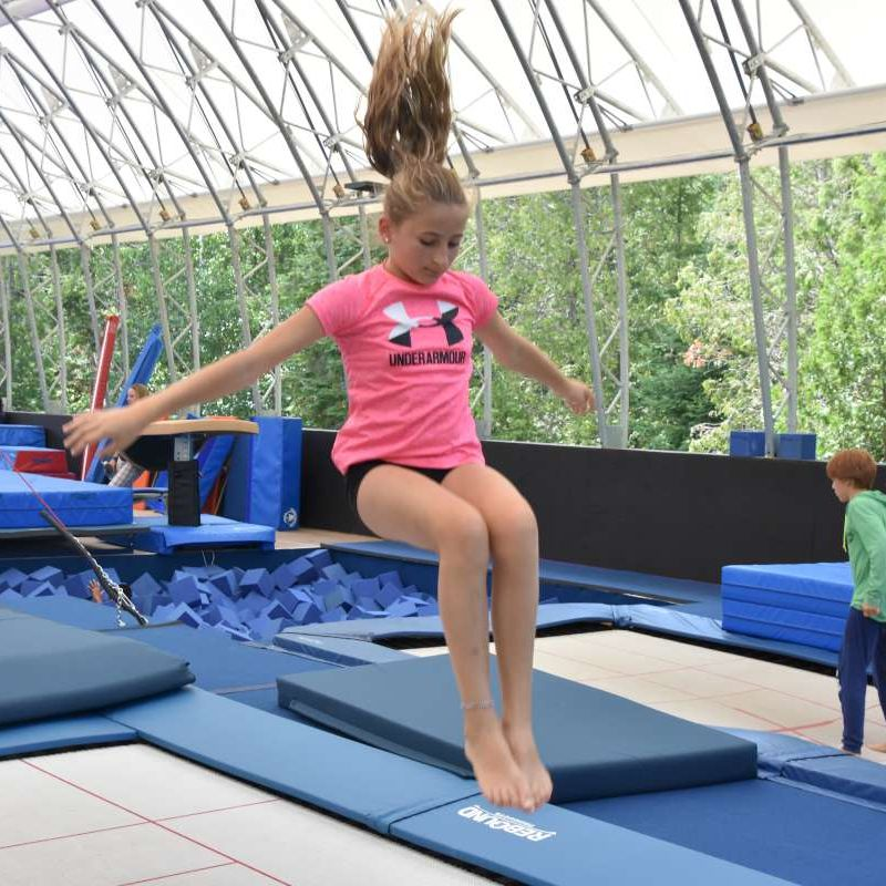 Girl camper doing a seat jump on the trampoline at Canadian Adventure Camp