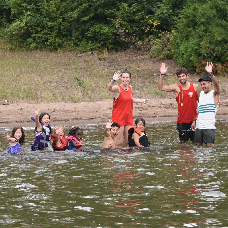 staff and campers at the beach waving at the camera