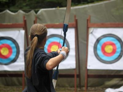 teenage camper at an archery session at camp