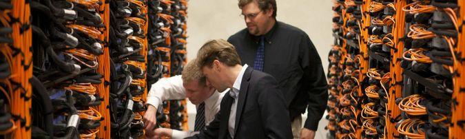 Three men fixing cables