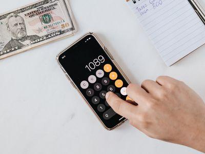 Bilde av en kalkulator som noen bruker til å telle penger med.