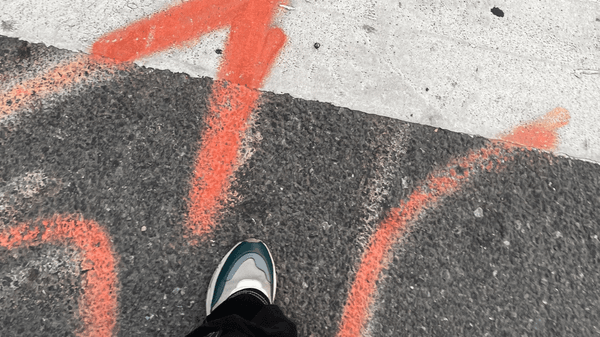 Orange spray paint in streets, which tells that communications cables are buried in the ground