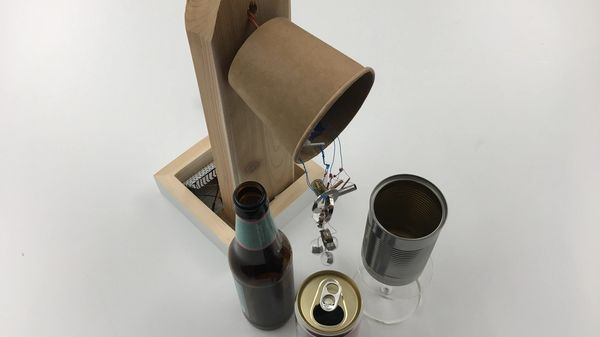 Photo of Sound Branch, an arduino instrument with metal pieces hanging and turning next to bottles