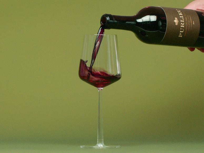 A hand pours a bottle of red wine into a wine glass on a green background.