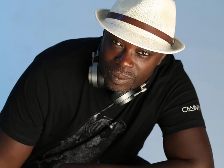 Peter Adjaye wearing headphones and a fedora, on a light blue background.