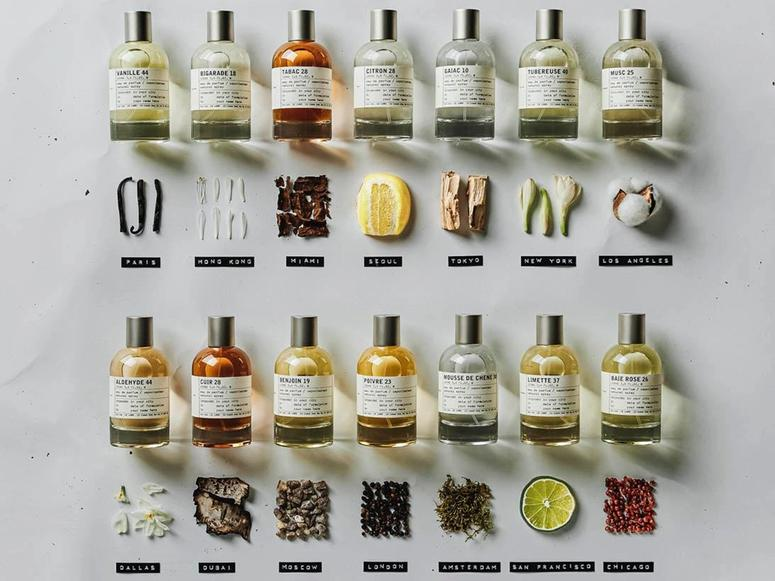 Fouteen Le Labo City Scents perfume bottles above an assortment of natural objects and their city names.