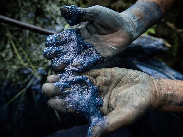 Two hands covered in indigo dye.