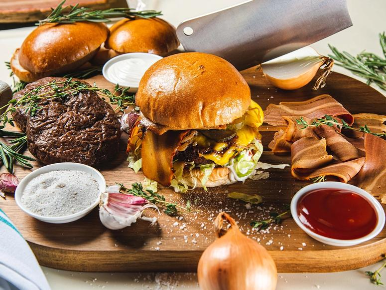 A carving board with vegan burgers and bacon, onions, a cleaver, herbs, and condiments.