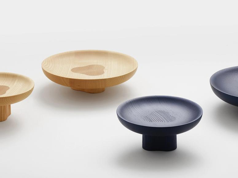 Black and natural wooden bowls on small, built-in platforms that raise them off the table.