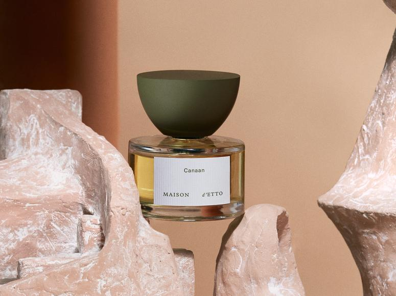 A sculptural bottle of perfume is balancing between two pieces of carved stone.
