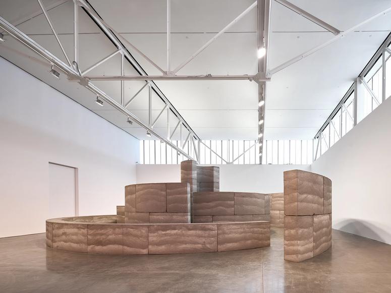 An earthen sculpture in a gallery.