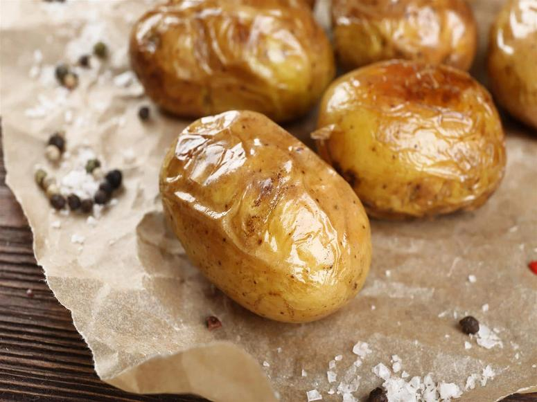 Baked potatoes sitting on wax paper with salt and pepper.
