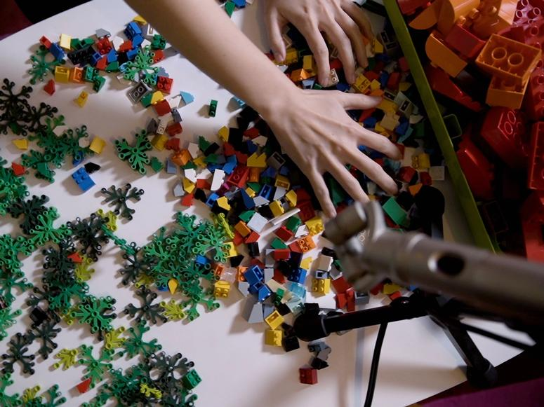 Two hands mixing up Lego pieces on a white table.