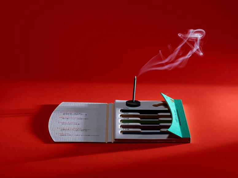 Incense burning on a pack of sticks on a red background.