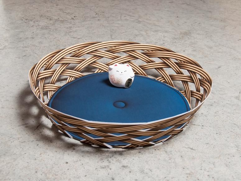 A round basket with a blue cushion and small cat figurine sitting inside.