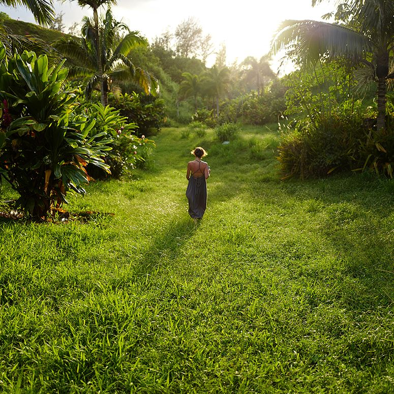 A woman walking in a field surrounded by palm trees.