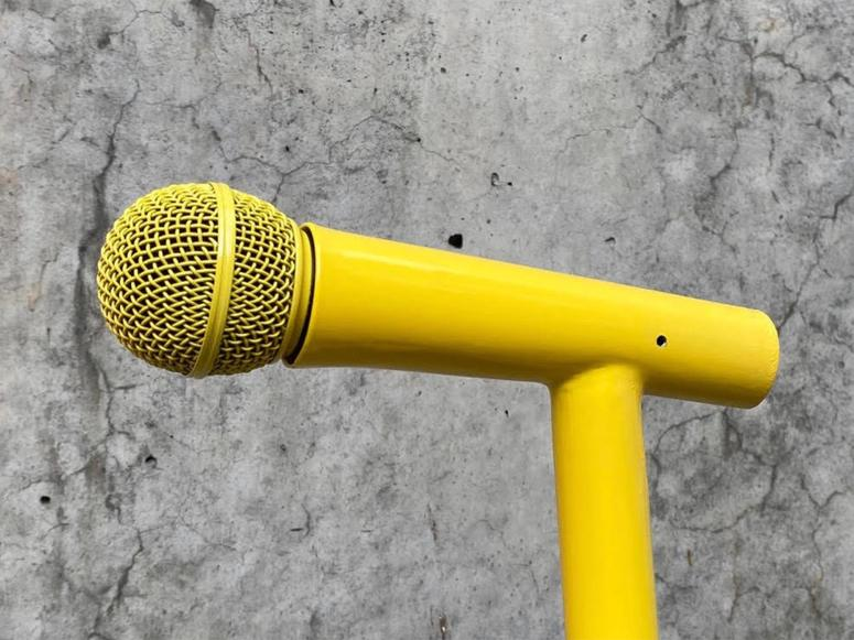 A yellow microphone on a concrete background.