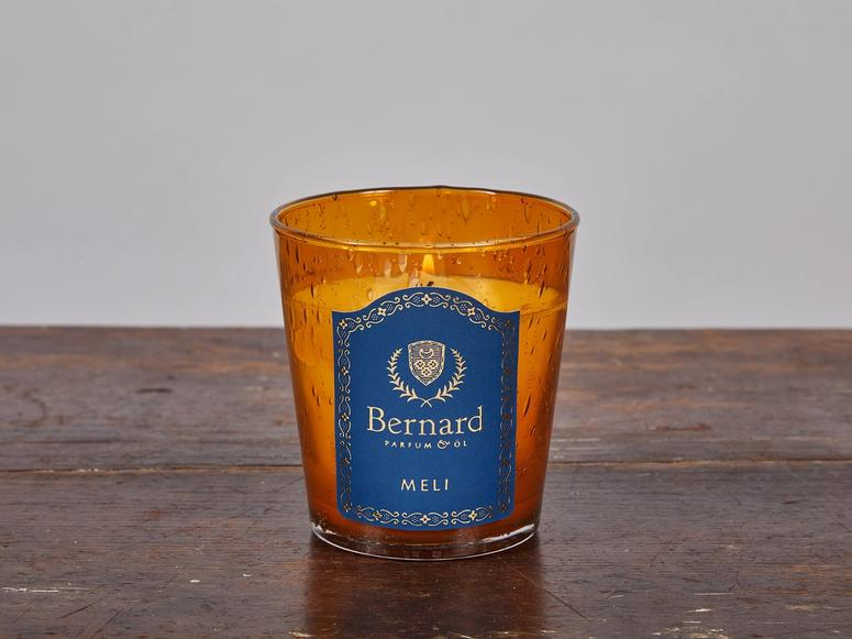 An orange and blue candle on a wood surface.