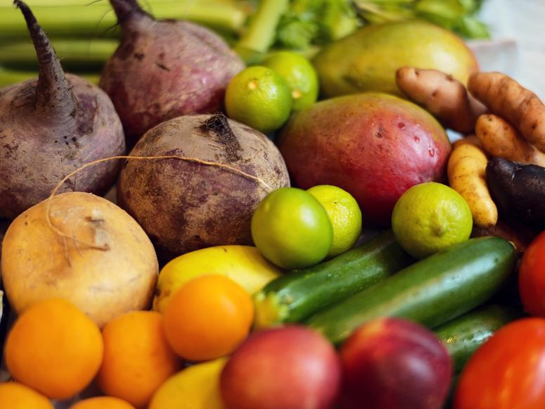 An assortment of brightly colored fruits and vegetables in close up.