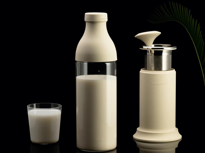 A white Modern Milk milk press and glass of milk on a black background.