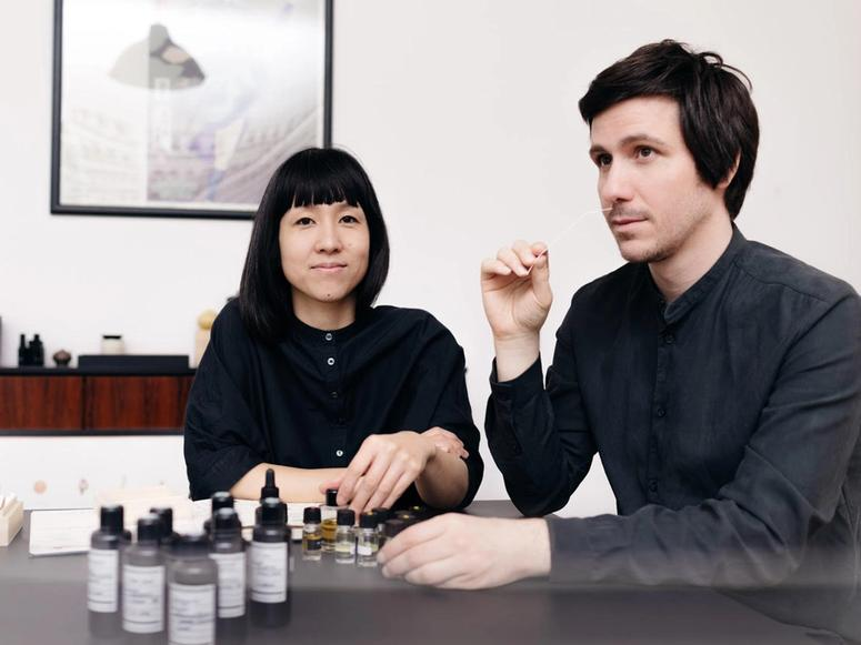 A woman and a man smelling bottles of fragrances.