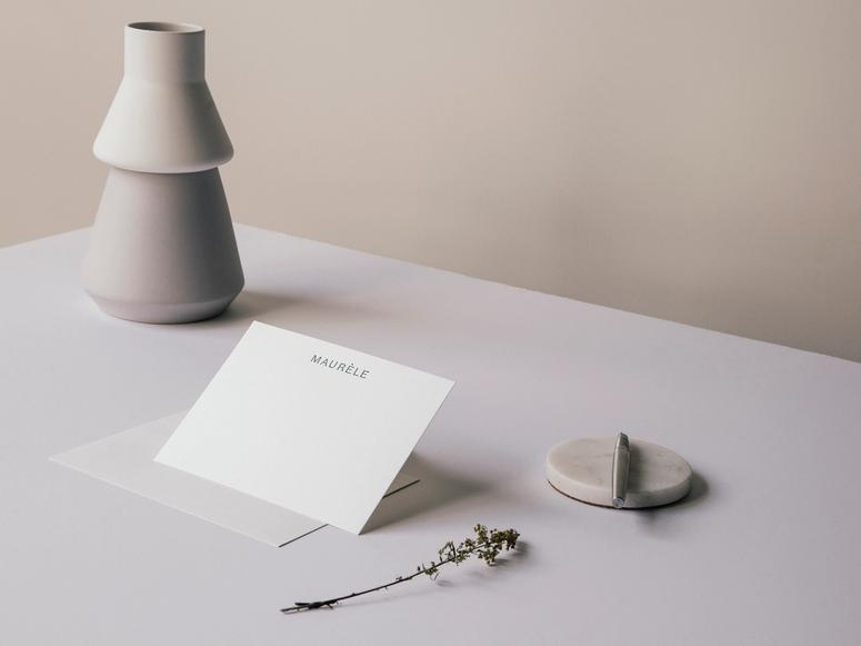 A note card on a desk with a pen, carafe, and sprig of herbs.